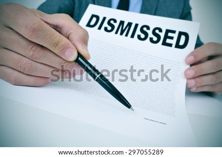 a young businessman sitting at his office desk shows a document with the word dismissed written in it and points with a pen where to sign - stock photo