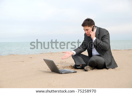 A young businessman sitting c in front of a laptop and talking on a mobile phone. - stock photo