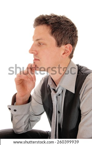 A young businessman sitting isolated for white background with one hand on his chin in a grey shirt, vest and tie.  - stock photo