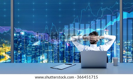 A young businessman sitting on a chair with hands on the back of his head in front of a panoramic window at night, graphs on the window. Concept of having a rest in office. - stock photo