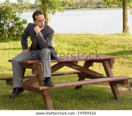 A young businessman sitting on a park bench outside, thinking of work