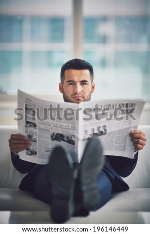 A young businessman sitting on sofa and reading newspaper - stock photo