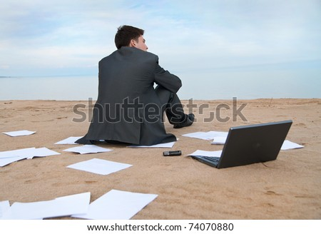 A young businessman sitting on the beach. Around it are scattered documents.