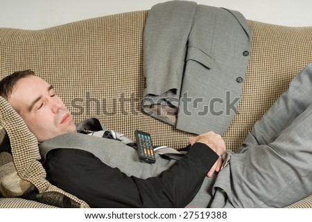 A young businessman sleeping on the sofa with a television remote on his belly - stock photo