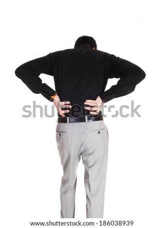 A young businessman standing from the back holding his hands on his back for heavy back pain, isolated for white background.  - stock photo
