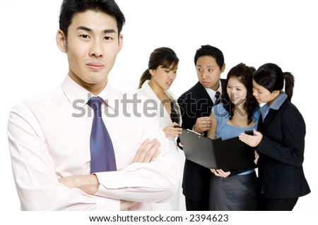 A young businessman standing in front of his business team on white background