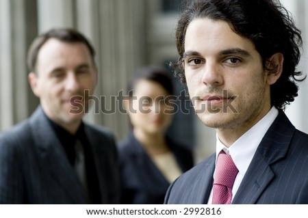 A young businessman standing in front of his team (shallow depth of field used)