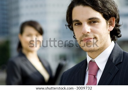 A young businessman standing outside with a female colleague behind (shallow depth of field used)