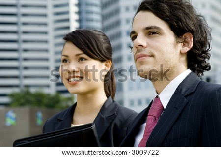 A young businessman standing outside with his female business partner with city in background (shallow depth of field used)