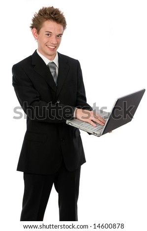 A young businessman standing up using a laptop - stock photo