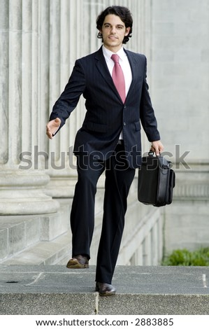 A young businessman stepping off a stone ledge