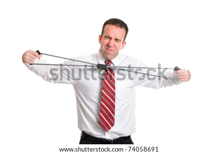 A young businessman straining to stretch a resistance band, isolated against a white background. - stock photo