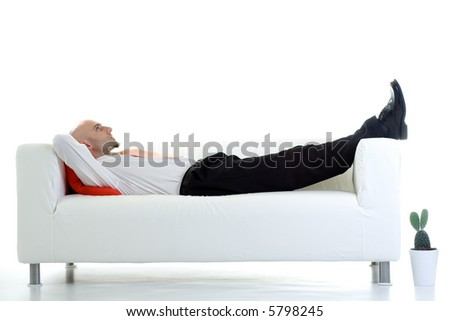A young businessman takes a short break and lies down on the couch. - stock photo