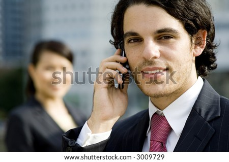 A young businessman taking a call outside with a female colleague standing behind out of focus