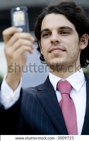 A young businessman taking his picture using mobile phone