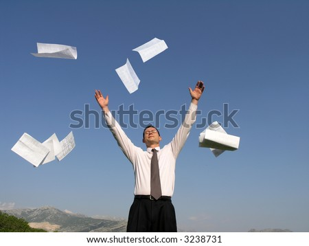 A young businessman throwing away his papers - stock photo