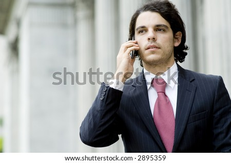 A young businessman using a mobile phone outside