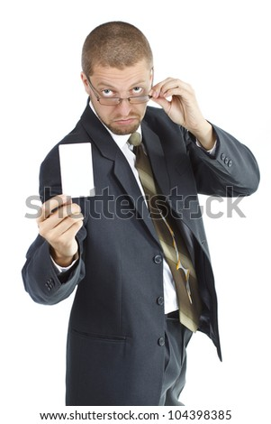 A young businessman wearing suit and tie is holding a blank card in his right hand, touching his glasses with his left hand and looking from behind his glasses - isolated on white - stock photo