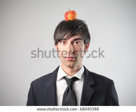 A young businessman with an apple on his head - stock photo