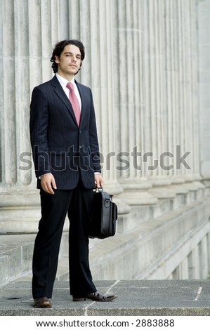 A young businessman with briefcase standing outside a great building
