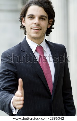 A young businessman with hand outstretched to greet someone