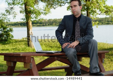 A young businessman working outside in a park