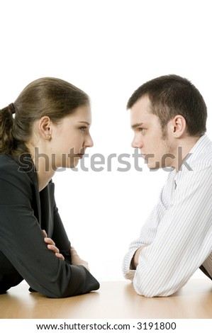 A young businesswoman and businessman staring at each other across a table