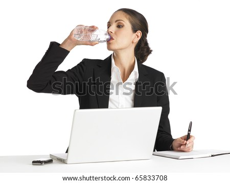 a young businesswoman drinking water at work. - stock photo