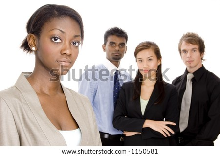 A young businesswoman (in focus) stands in front of her diverse business team (off focus)