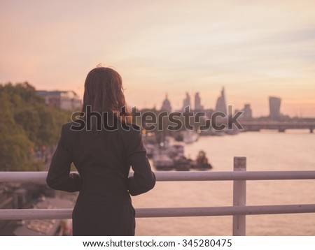 A young businesswoman is standing on a bridge at sunrise and is admiring the London skyline - stock photo