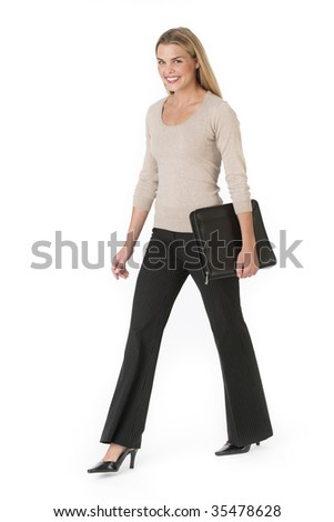 A young businesswoman is walking and carrying a notebook.  She is smiling at the camera.  Vertically framed shot.