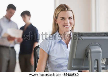 A young businesswoman is working on a computer while her coworkers are talking in the background.  She is smiling at the camera.  Horizontally framed shot. - stock photo