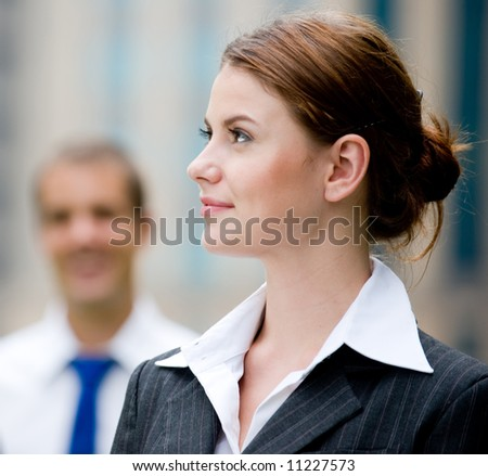 A young businesswoman standing outside with male colleague standing behind - stock photo
