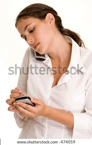 A young businesswoman takes notes on her PDA whilst on the phone - stock photo