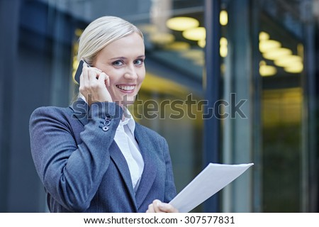 A young businesswoman talking on her cellphone outside, holding documents - stock photo