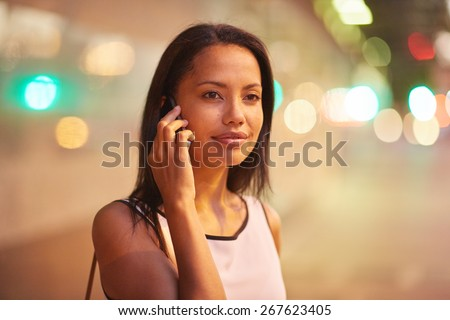 A young businesswoman talking on her phone while standing in front of an office block - stock photo
