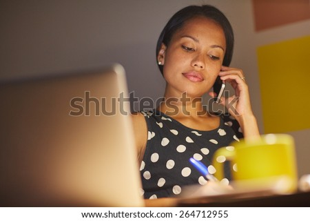 A young businesswoman talking on the phone while sitting in front of her laptop at night - stock photo