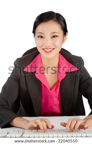 A young businesswoman typing at her desk