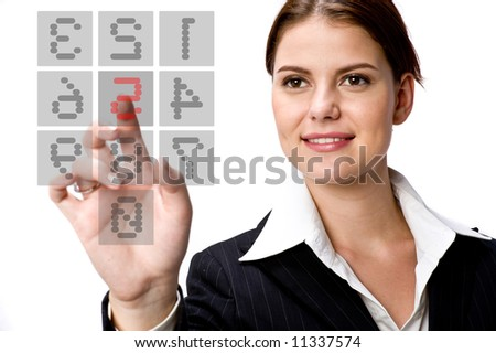 A young businesswoman typing on a transparent keypad on screen - stock photo