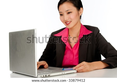 A young businesswoman using a credit card on the computer - stock photo