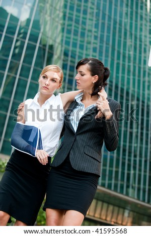 A young businesswoman with injured arm and bandages walking and supported by a friend - stock photo