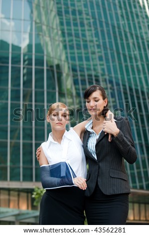 A young businesswoman with injured arm and bandaids walking and supported by a friend - stock photo