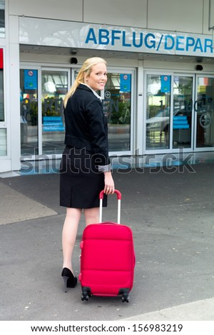 a young businesswoman with suitcase on an airport. - stock photo
