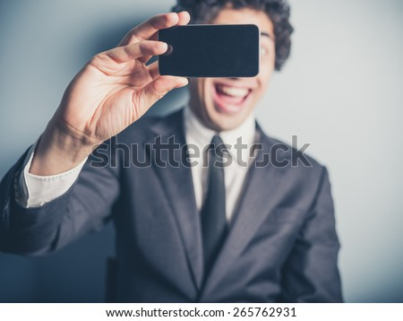 A young busnessman is using his smartphone to take a selfie - stock photo