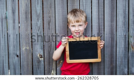 A young by wearing a red shirt is standing against a rustic wooden fence holding a blank blackboard.