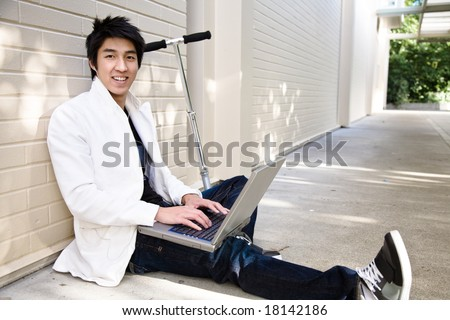 A young casual asian male using a laptop and listening to music - stock photo