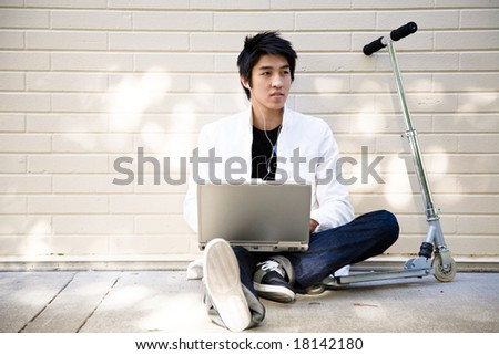 A young casual asian man using laptop and listening to music