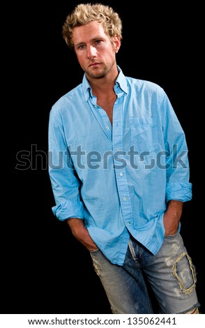 A young, Caucasian, blue eyed, blonde haired male. He is wearing a blue button up shirt, blue jeans and has his hands in his pockets. - stock photo