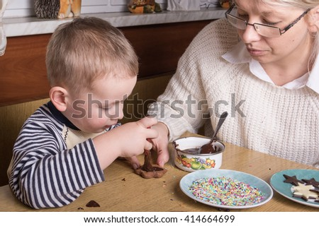 a young caucasian boy decoratingcookies - stock photo