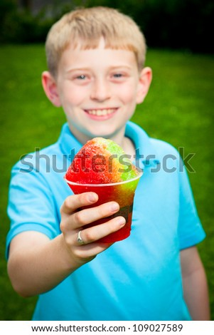 A young Caucasian boy holds a snow cone as he smiles at the camera. - stock photo